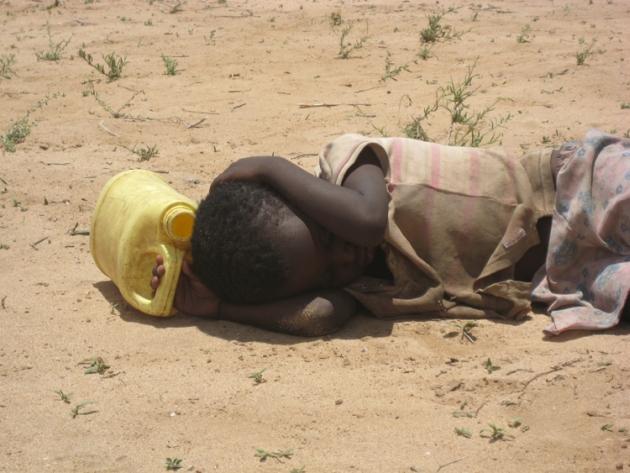 Ein hungerndes und durstendes Kind wartet im Staub liegend auf die Ausgabe von Essen und Wasser.